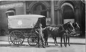 A Union Meat Company deliveryman in a jaunty pose with his team. The horses wear Teamster emblems on their headgear. 1910